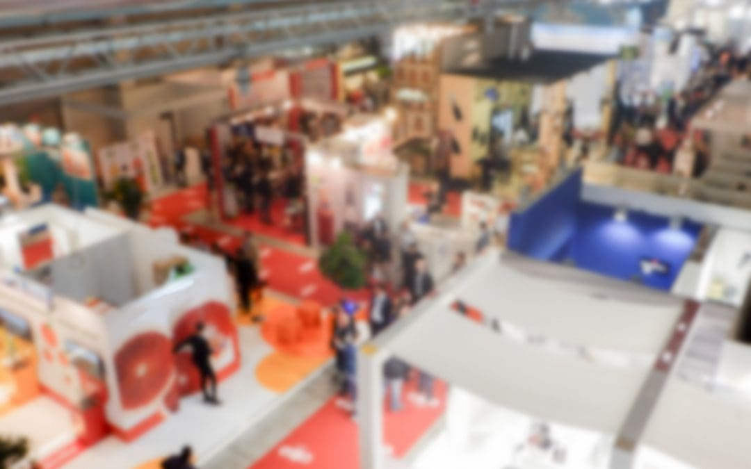 Defocused background of the Pack Expo trade show with people visiting the commercial exhibition. Intentionally blurred post production for bokeh effect